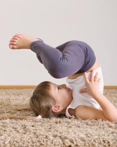 Cute little girl yoga exercising